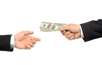 Hand handing over money to another hand