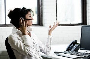 Young woman virtual assistant with headset and computer