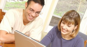 Smiling husband and wife looking at screen of laptop