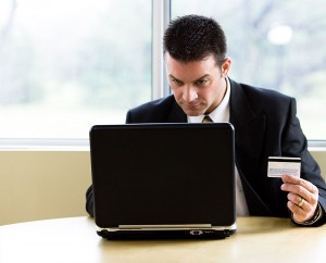 Man holding credit card in left hand and working with laptop