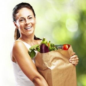 Smiling woman with a groceries in a sack