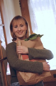 Smiling woman hugging sack of groceries