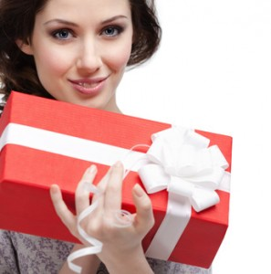 Smiling woman holding gift wrapped in red paper