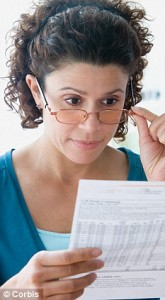 Woman holding glasses with one hand while examining statement