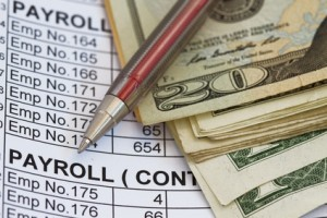 Pen and money on top of payroll information