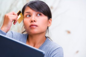 girl thinking while holding a credit card