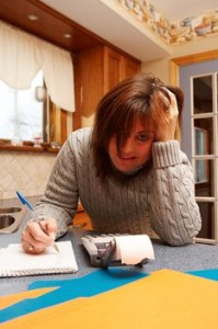 frustrated woman with a pen, paper and calculator