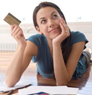 woman holding a credit card, thinking