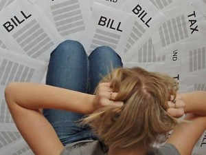 woman kneeling over several bills