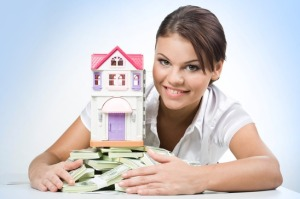 woman holding a house and some cash