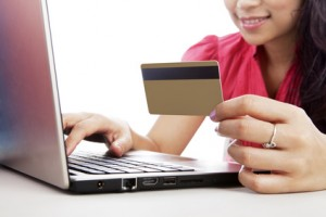 Woman-holding-credit-card-and-looking-a-laptop-300x200