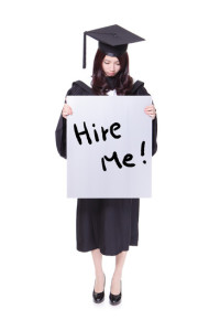 "woman graduate student standing up with a ""hire me"" sign"