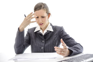 Frustrated business woman having problems with analyzing documents.