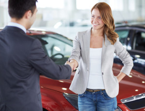 Woman closing a deal with a car salesman with a handshake