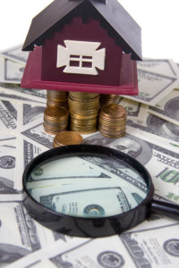 House and magnifying glass of one hundred dollar bills background