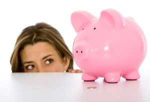 woman looking at her piggy bank