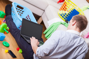Man using laptop sitting on the floor in dirty drawing room