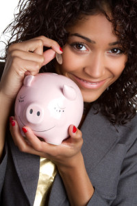 Beautiful woman saving money in piggy bank