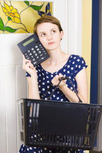 Woman holding a grocery basket and a calculator