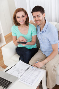 young happy couple calculating budget