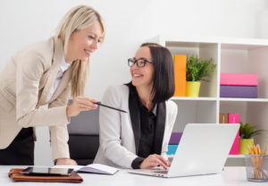 Two girls in the office in front of a laptop