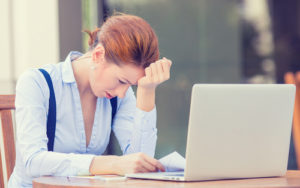 stressed displeased worried woman sitting in front of laptop computer
